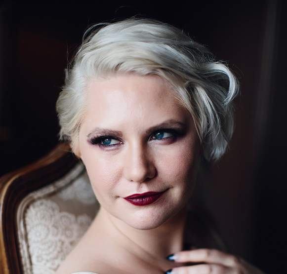 Writer, Vince Ruston, is sitting on a chair, body facing the side and head turned to face the camera. Their eyes are looking down to the right. They have dark red lipstick on and blonde, white hair.