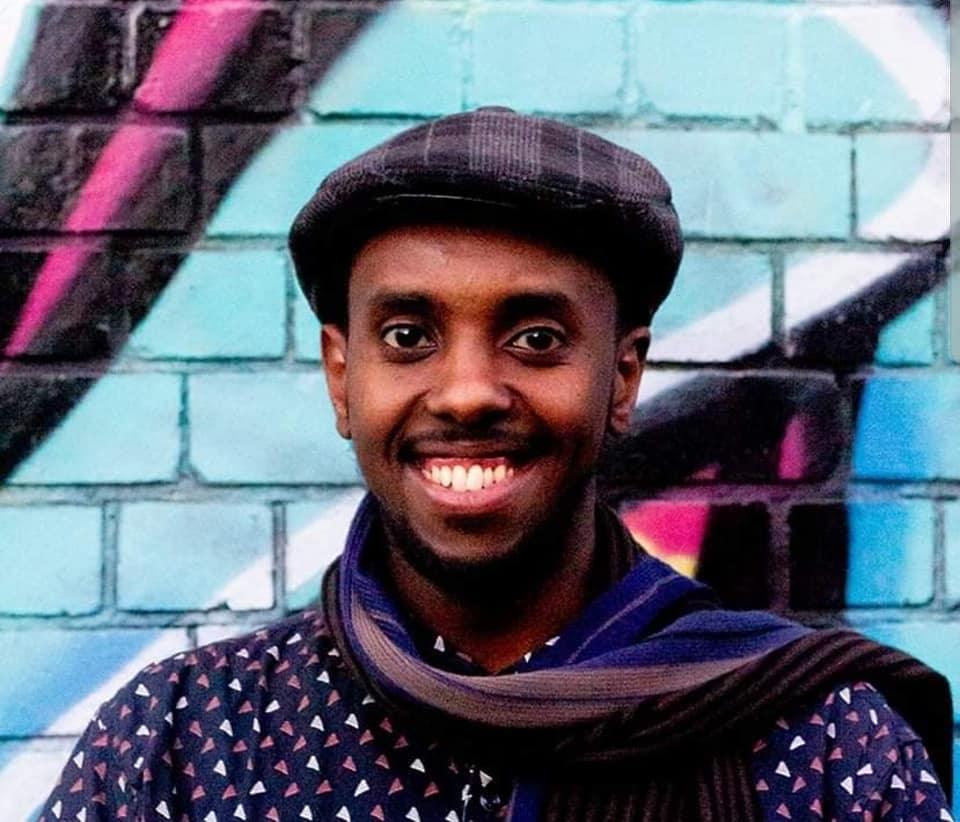 Writer, Awale Ahmed, standing front on wearing a blue top with a pattern on small white and purple triangles, a scarf and hat. They are smiling and standing in front of a graffiti wall.