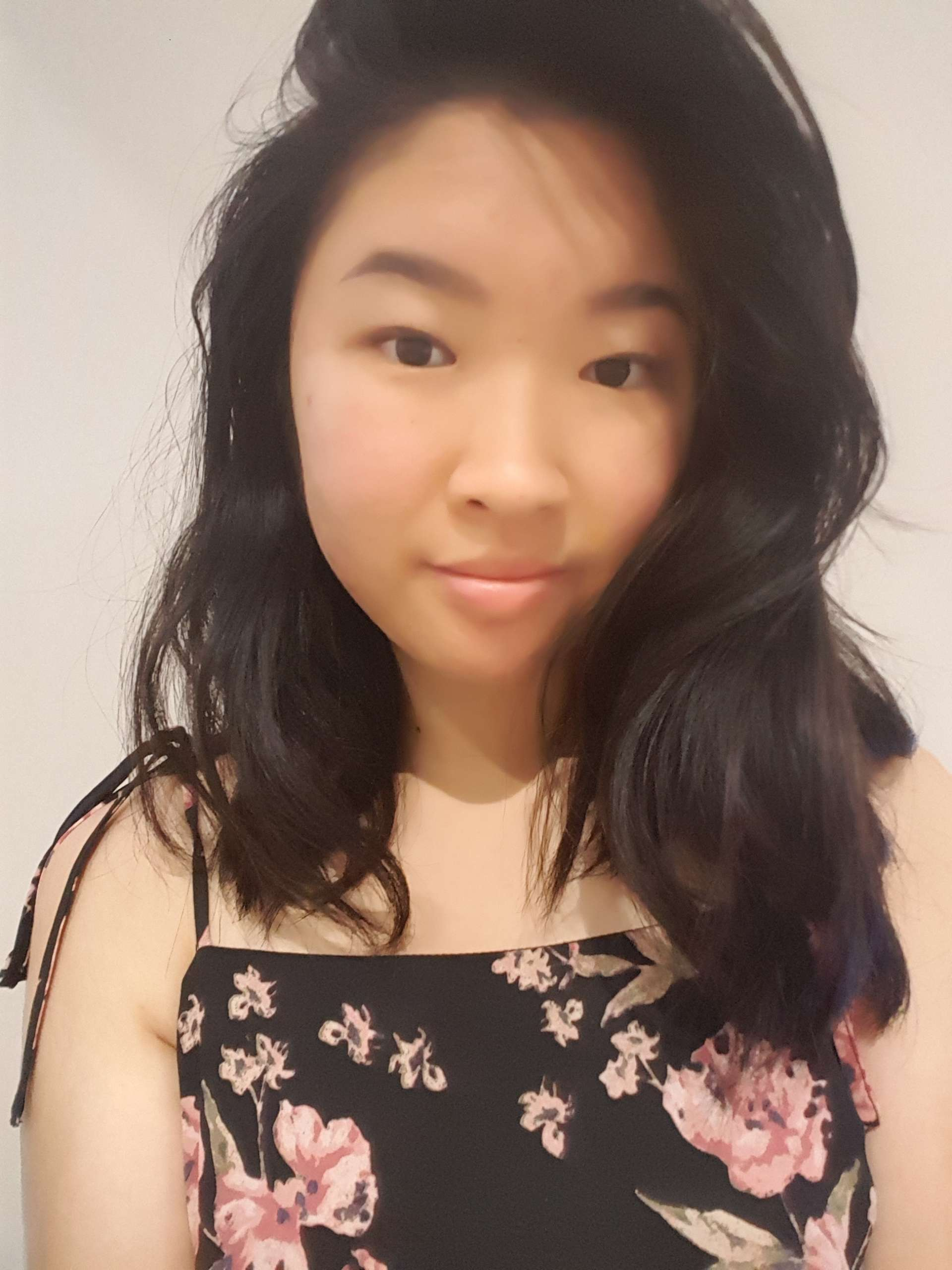 Writer, Christy Tan, weaing a black top with pink and green flowers. They are facing front on with long dark wavy hair parted on the right hand side.