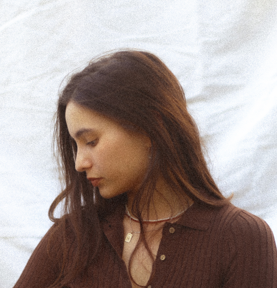 Writer, Kasumi Borczyk wearing a brown top, looking down at their right shoulder. They have long brown hair draped over their shoulders and the sunlight hits their hair from the right-hand side.