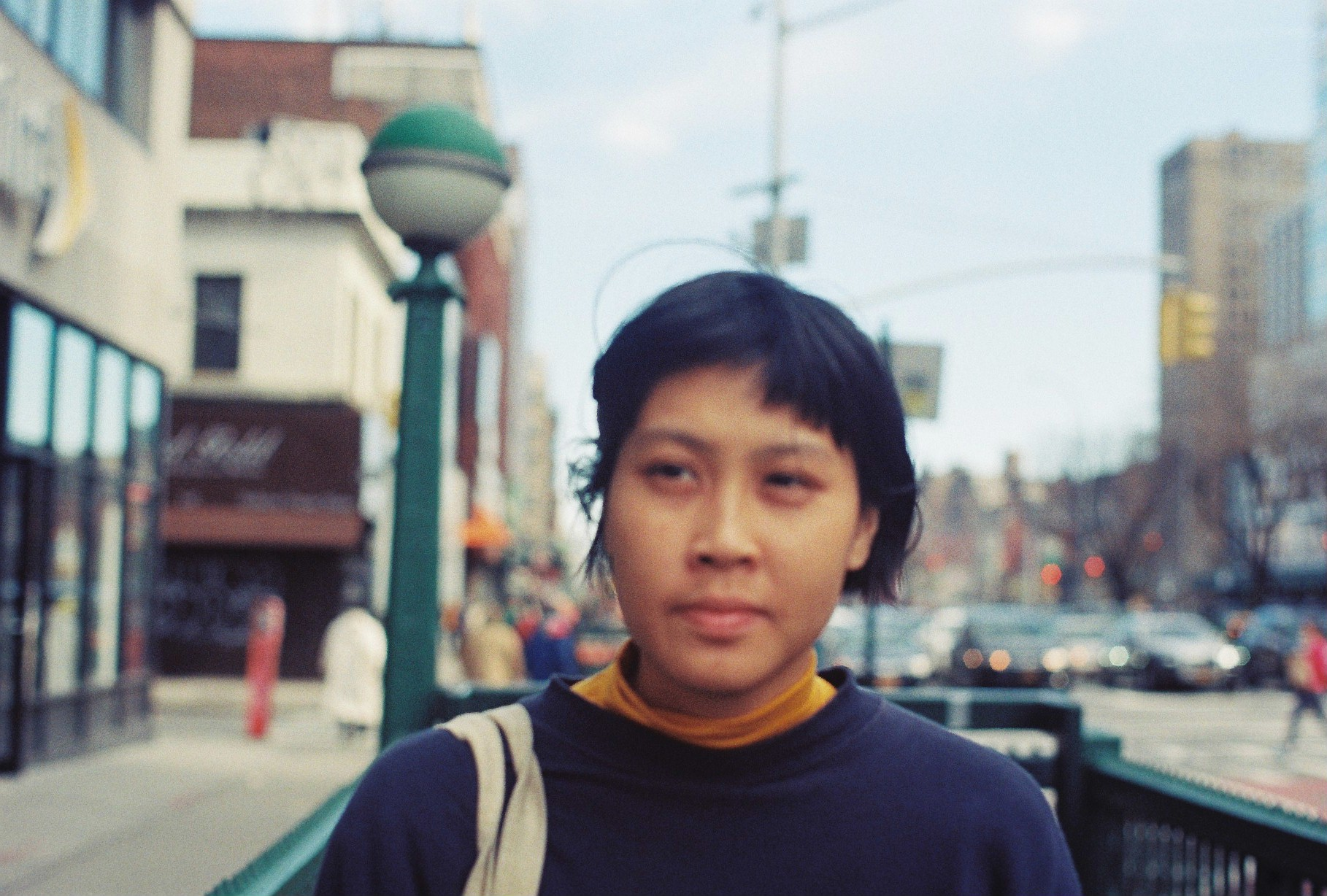 A headshot of Thao Ly, taken on the street. Thao is wearing a dark blue sweater and has a light coloured tote over her right shoulder. Thao looks off camera to the left. The street is blurred behind her.