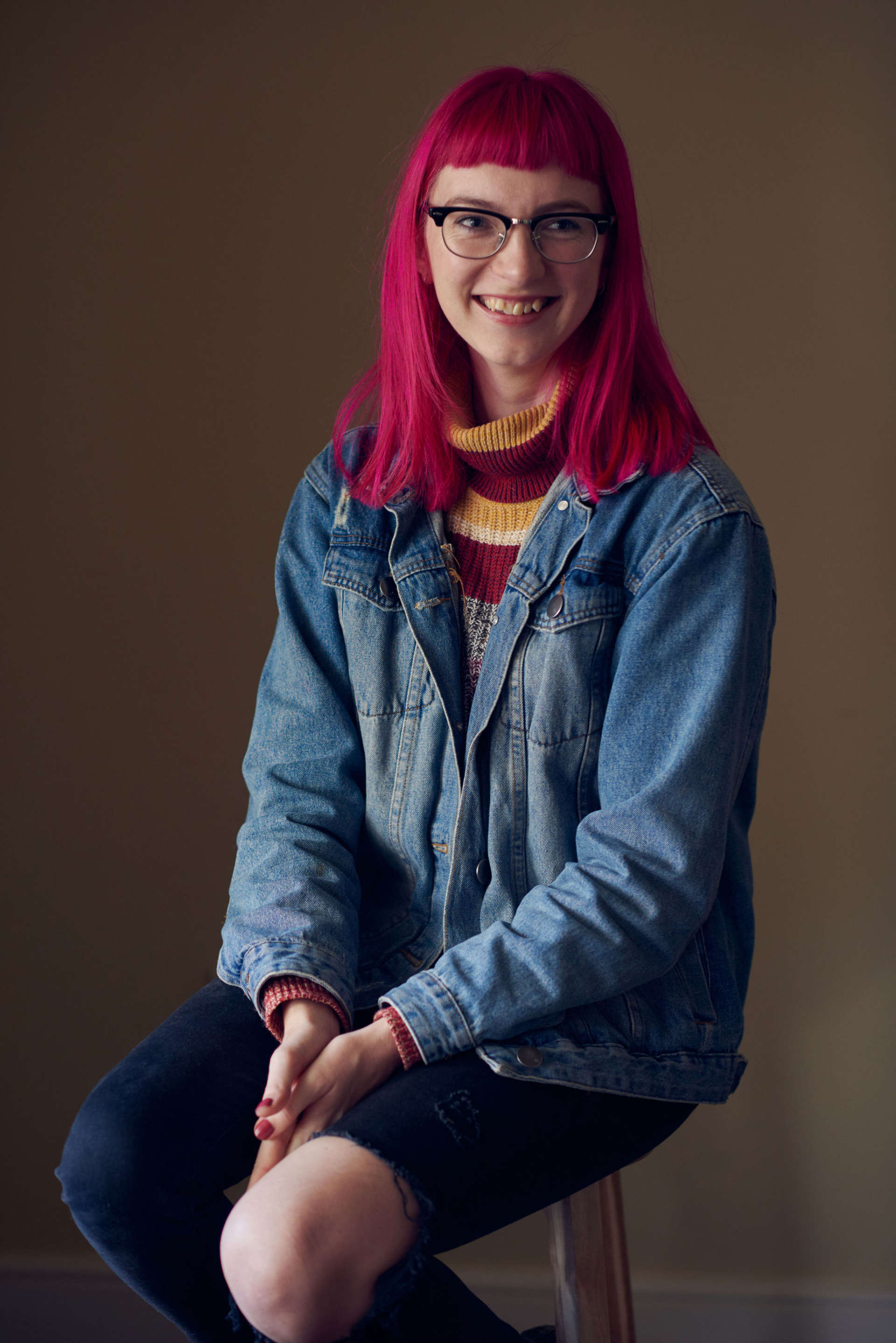 A headshot of the writer Josephine Newman. Jospehine has long dark pink hair and is wearing glasses. She is smiling at the camera.