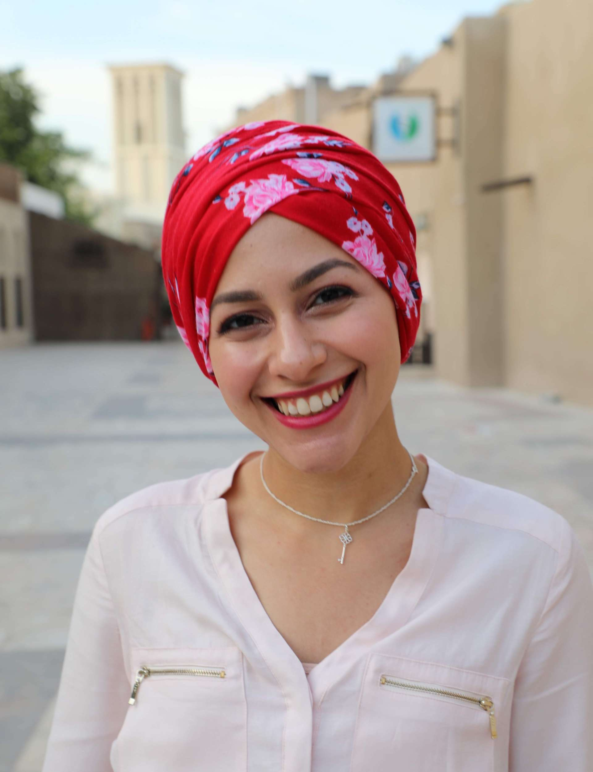 A headshot of Lur Alghurabi wearing a white long sleeved shirt, silver necklace, red lipstick and a red scarf with pink flowers wrapped around her head. She is smiling at the camera and the background is of a blurry outside setting.
